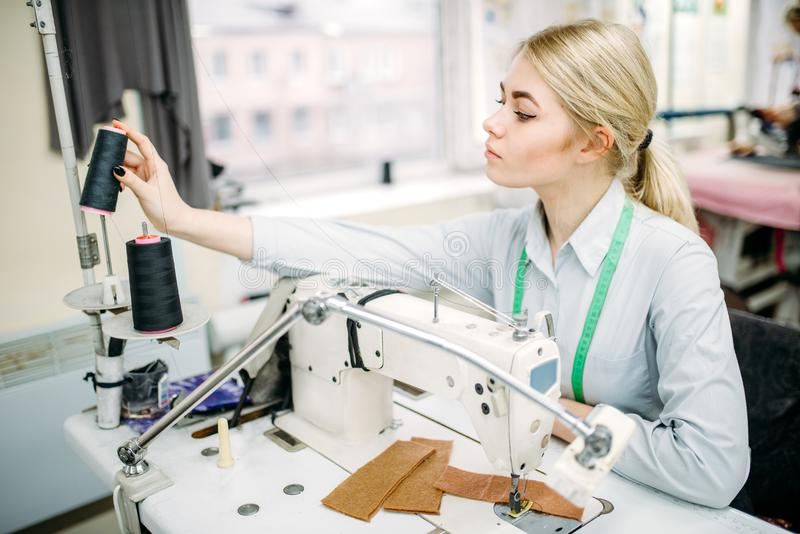 Female dressmaker sews on serger machine stock photography