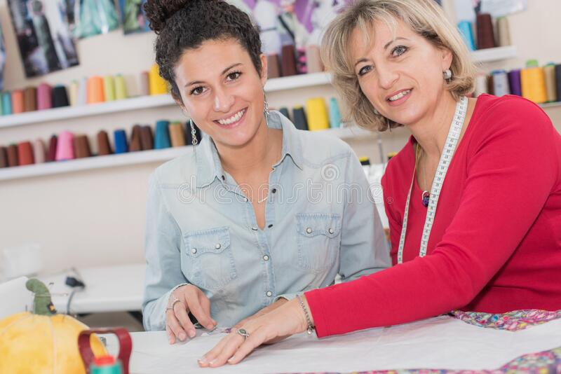Female dressmakers marking out pattern on cloth royalty free stock photography