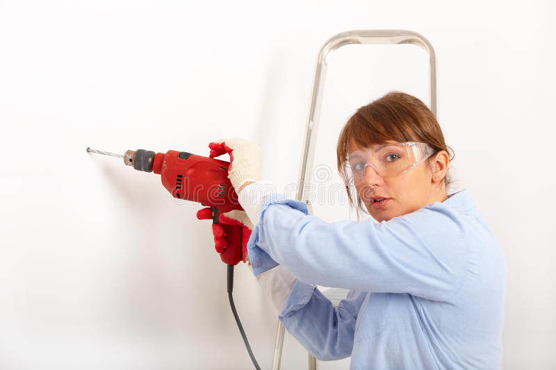 Female drilling hole royalty free stock photography