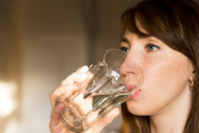 Female drinking from a glass of water. Health care concept photo. Lifestyle, close up royalty free stock photo