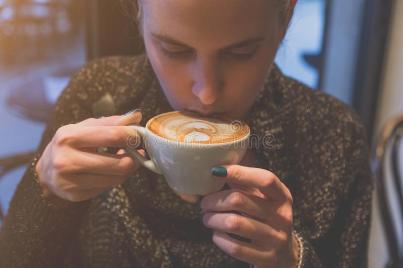 Female drinking latte in cafe stock photography