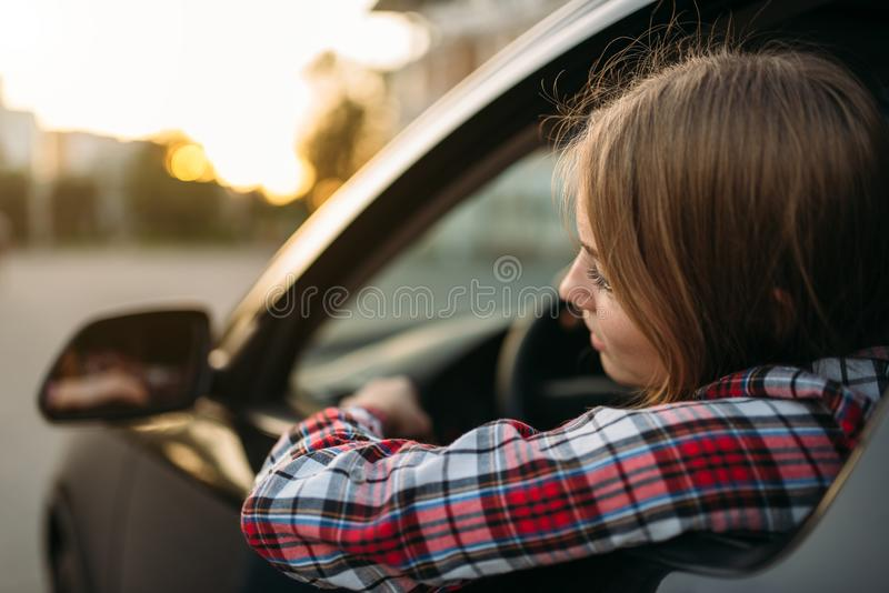 Female driver beginner looks out of the car window royalty free stock photography
