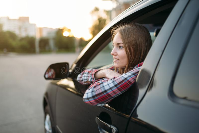Female driver beginner looks out of the car window stock image