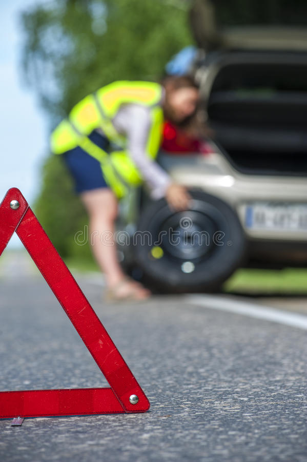 Female driver changing tire after breakdown stock photo