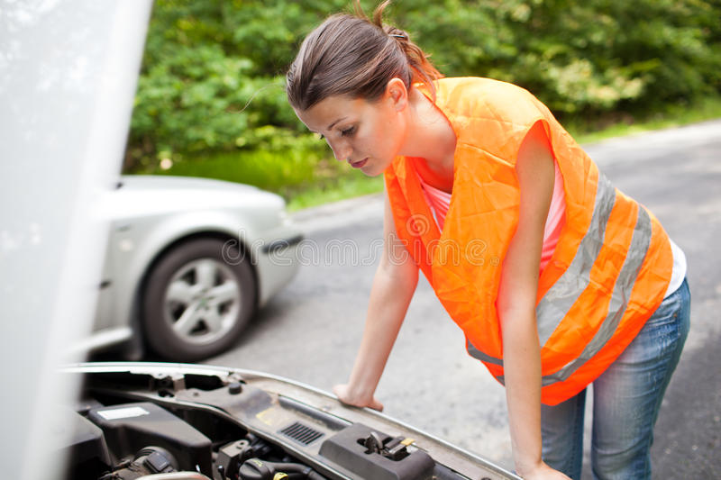 Female driver over the engine of her broken down c stock image