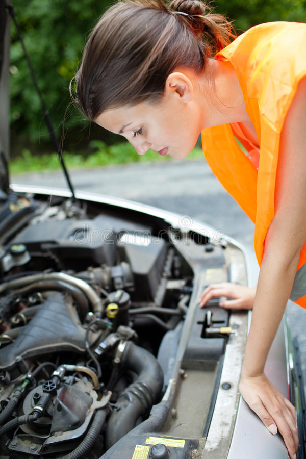 Female driver over the engine of her broken down c stock photos