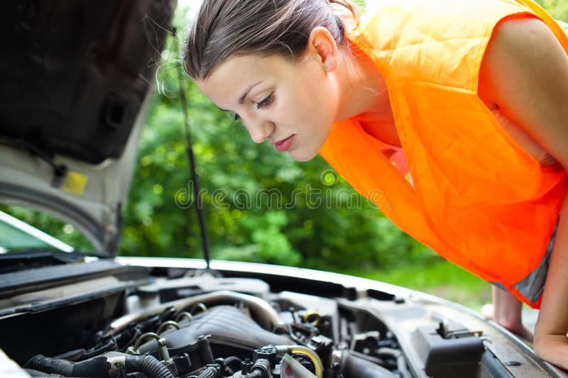 Female driver over the engine of her broken down c stock photo