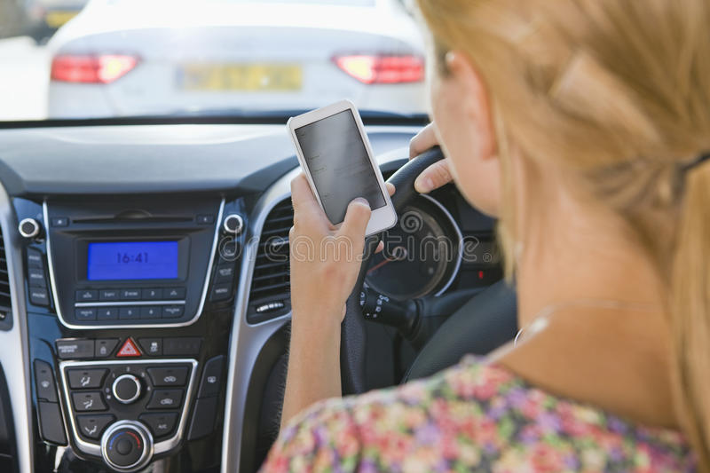 Female Driver Sending Text Message Whilst Driving royalty free stock photos