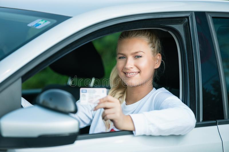 Female driving student showing drivers license. Driving school. Attractive young woman proudly showing her drivers license. Free space for text. Copy space royalty free stock images