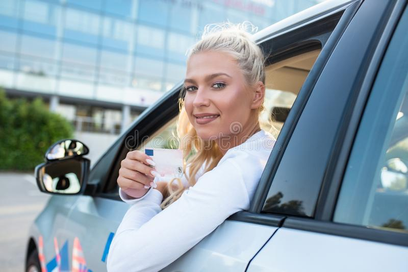 Female driving student showing drivers license. Driving school. Attractive young woman proudly showing her drivers license. Free space for text. Copy space. Lens stock photos