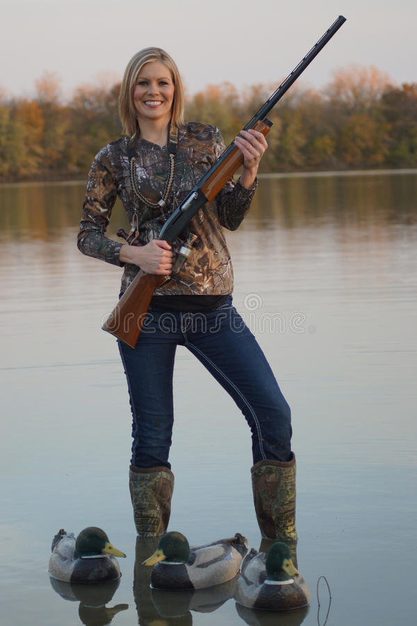 Female Duck Hunter with shotgun and decoys. A happy female duck hunter with her shotgun and decoys stock photo