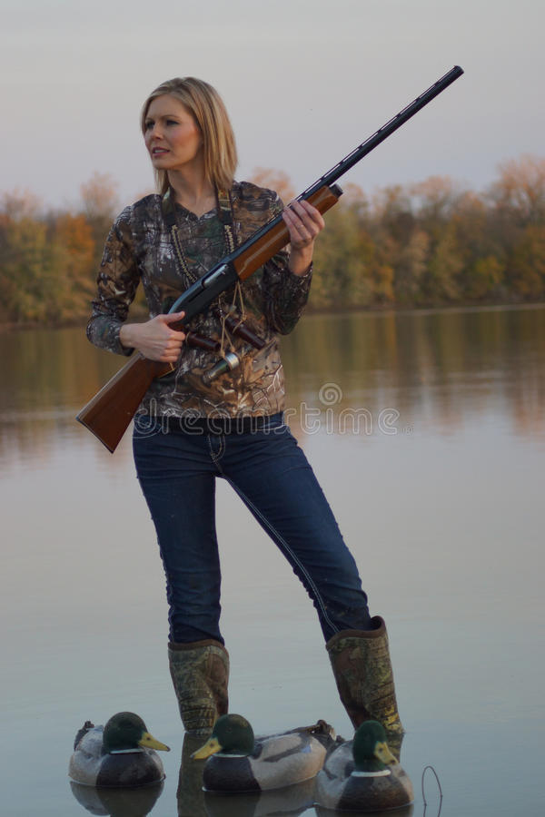 Female Duck Hunter with shotgun and decoys. A female duck hunter with her shotgun and her decoys royalty free stock photo