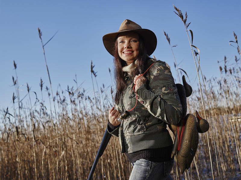Female duck hunter. Waterfowl hunting, smiling female hunter carry a shotgun and a decoys, reeds and blue sky on background stock images