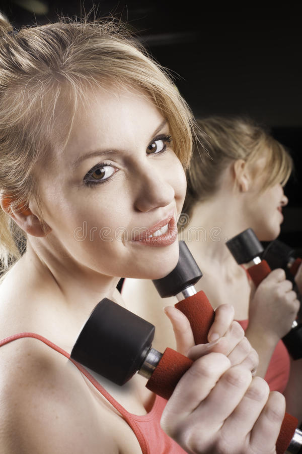 Female with dumbells. royalty free stock image