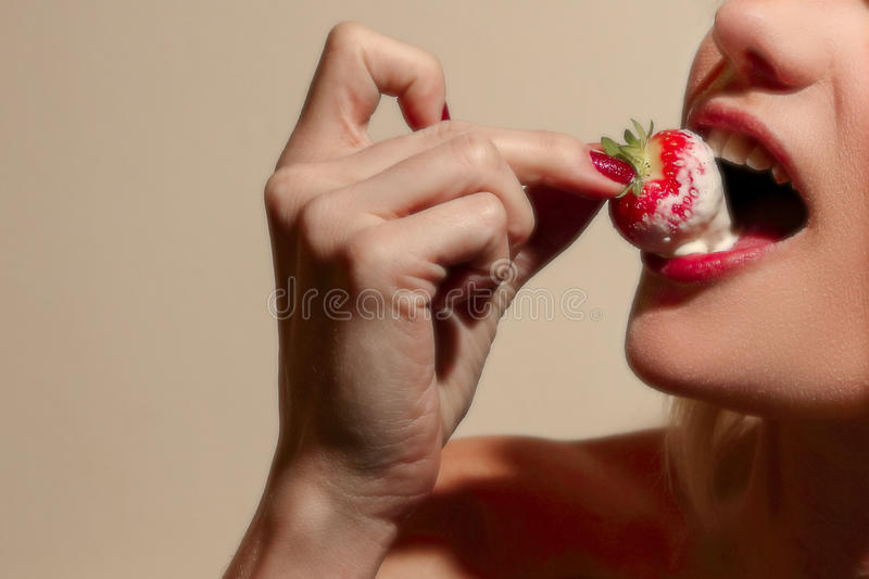 Female eating a strawberry covered in cream royalty free stock photography
