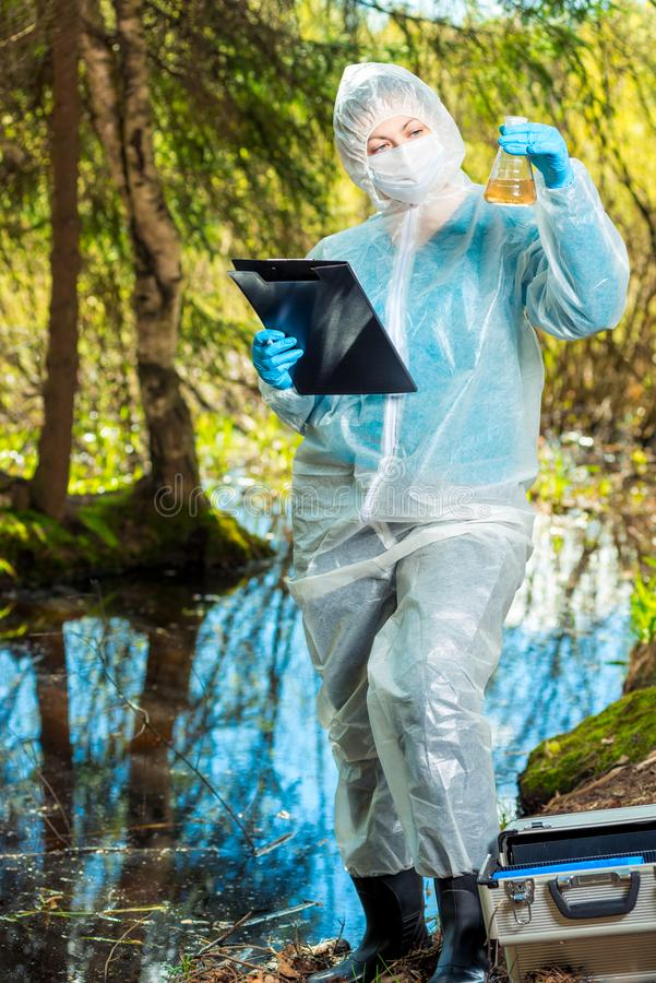 A female ecologist analyzes the state of water in a forest river and records the result of research stock image
