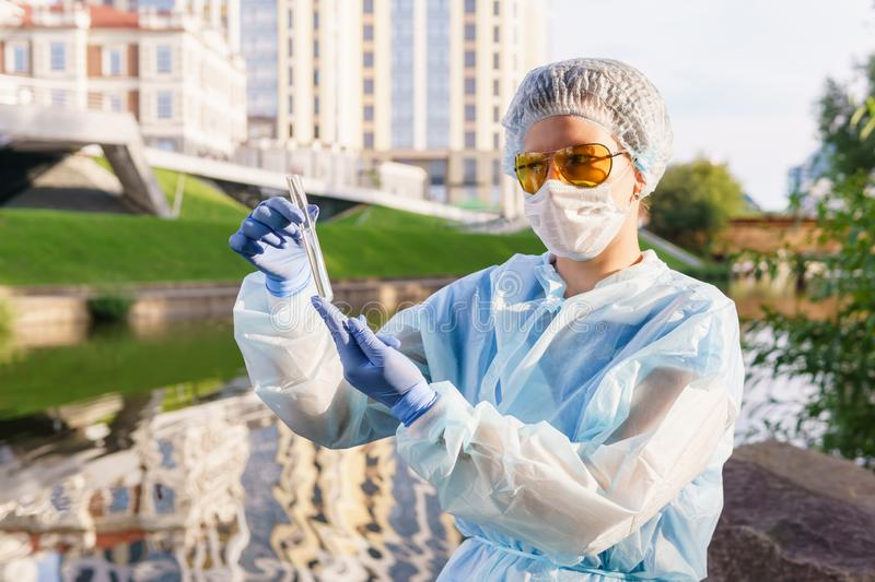 Female ecologist or epidemiologist checks water quality in urban canal. Female ecologist or epidemiologist visually assesses the quality of water in an urban stock image