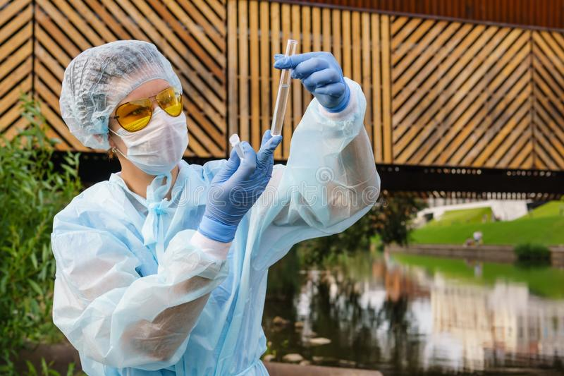 Female ecologist or epidemiologist checks water quality in urban pond. Female ecologist or epidemiologist visually assesses the quality of water in an urban stock photos