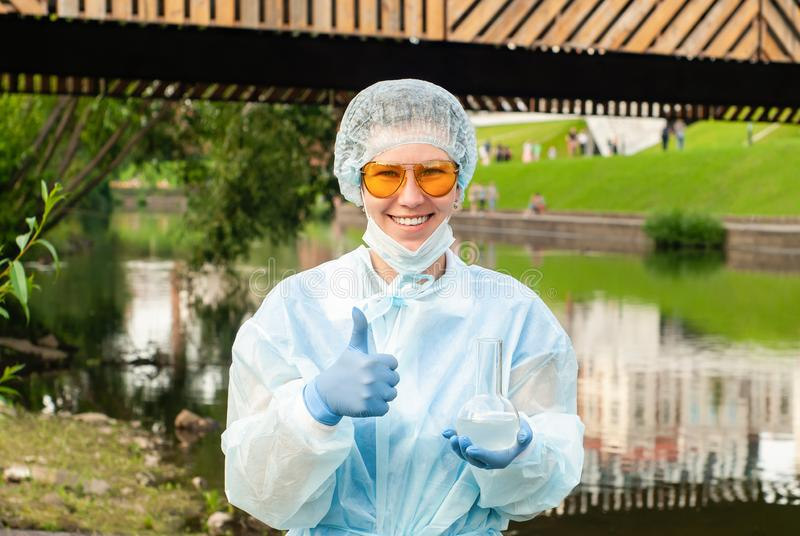Female ecologist or epidemiologist points to excellent urban water quality. Female ecologist or epidemiologist gestures for excellent quality of water, holding a royalty free stock photography