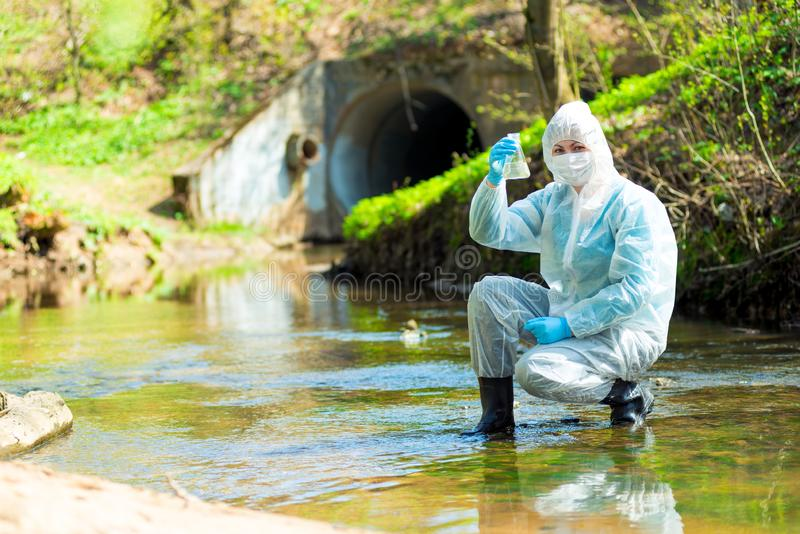A female ecologist takes water. From a sewage discharge stock photo