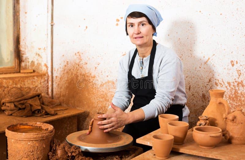 Female elderly master among the pottery. Glad elderly master among the pottery at the workshop royalty free stock images
