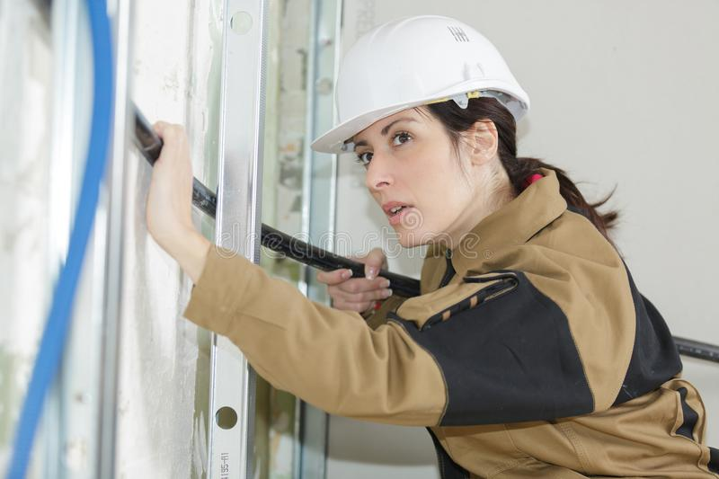 Female electrician fitting conduit in wall at construction site. Female stock photos