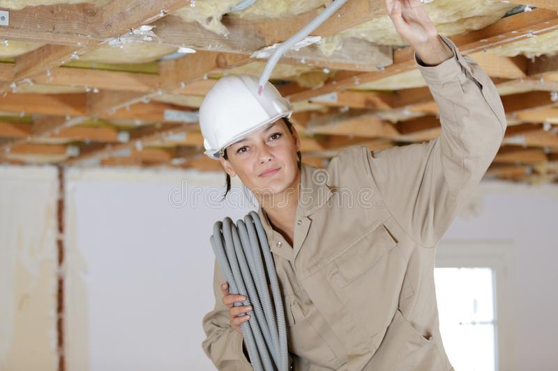 Female electrician fixing ceiling lighting royalty free stock photography