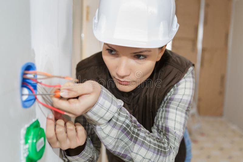 Female electrician fixing electric cables in socket stock image