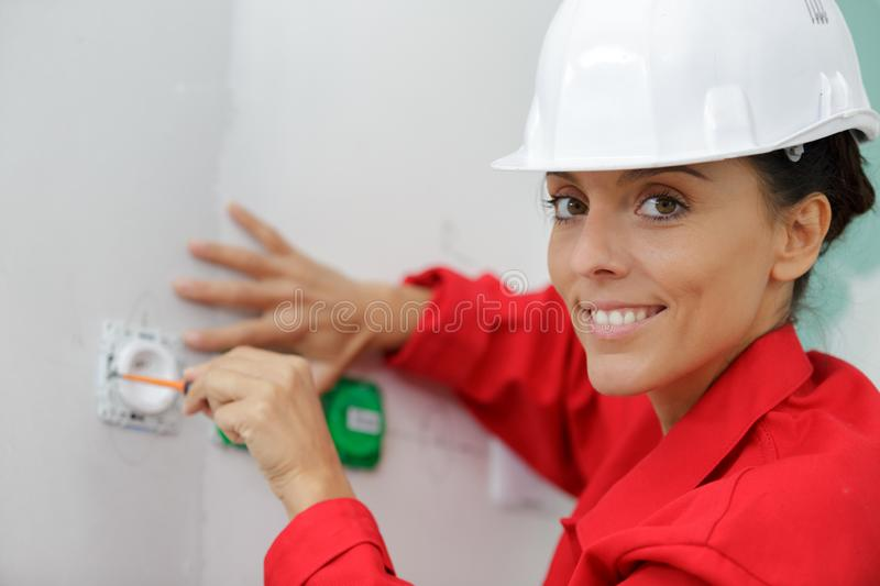 Female electrician fixing socket electricity problem royalty free stock image