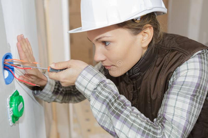 Female electrician fixing socket electricity problem royalty free stock images