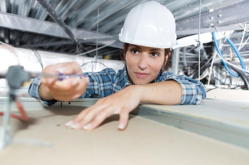 Female electrician installing electric device in ceiling stock image