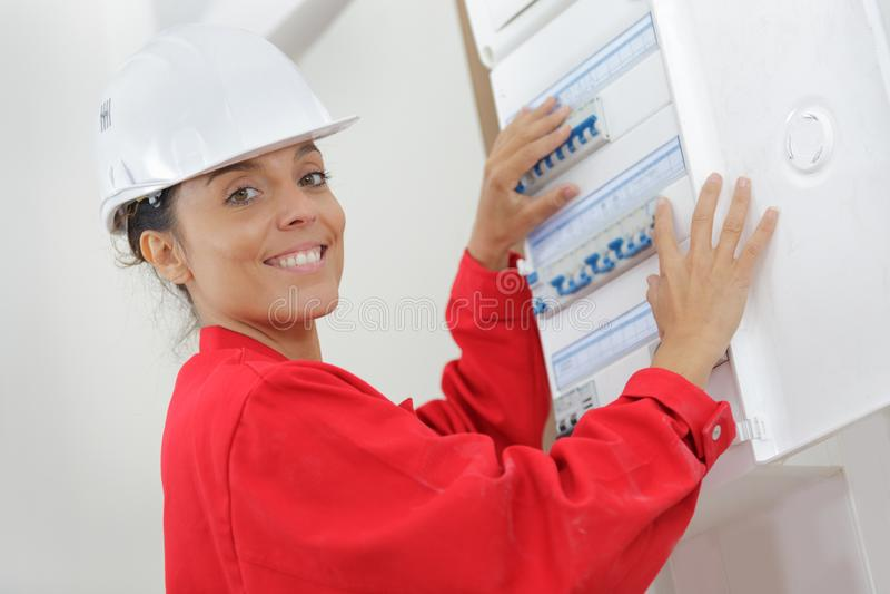 Female electrician installing energy saving meter royalty free stock photos