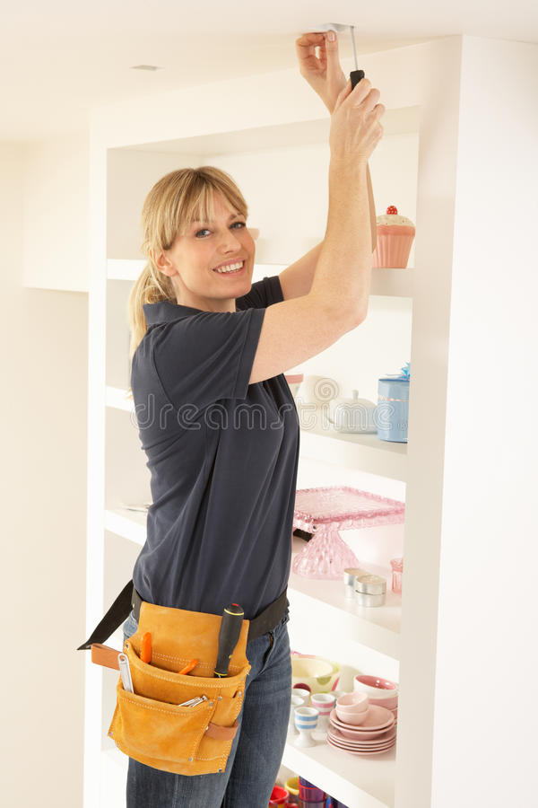 Female Electrician Installing Light stock images