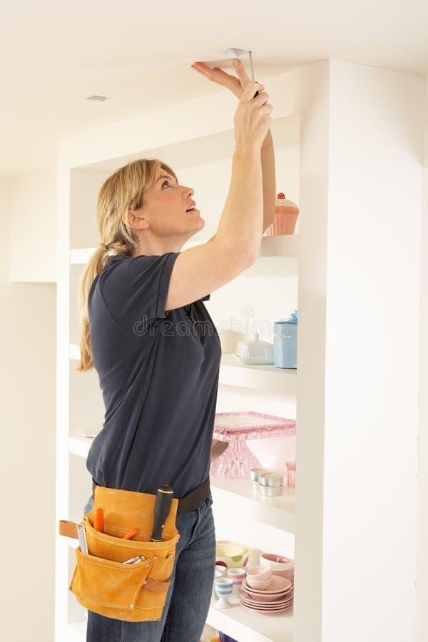 Female Electrician Installing Light stock photos