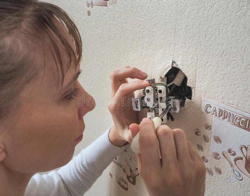 Female electrician repair the outlet on the wall. royalty free stock photo