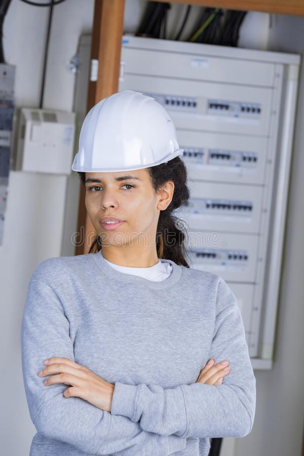 Female electrician standing in front open fuse box stock photo