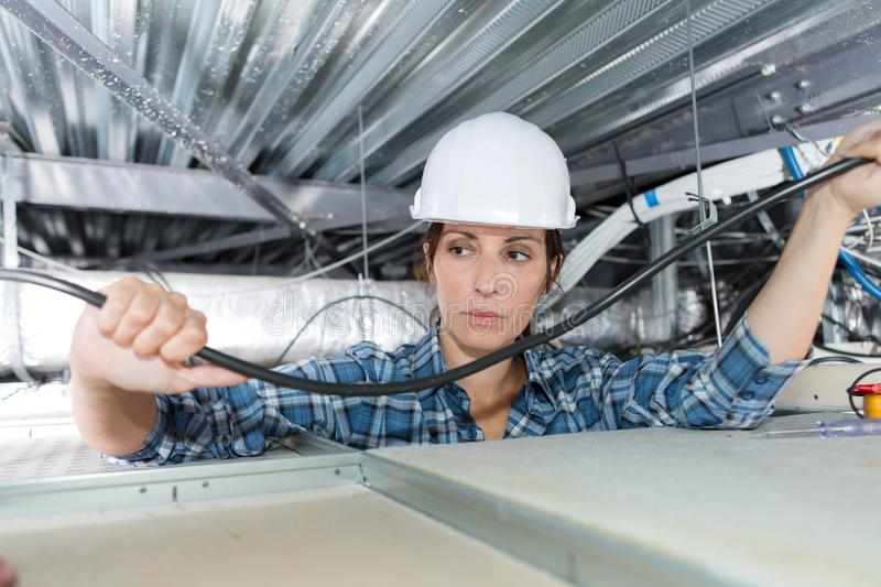 Female electrician wiring in building ceiling royalty free stock image