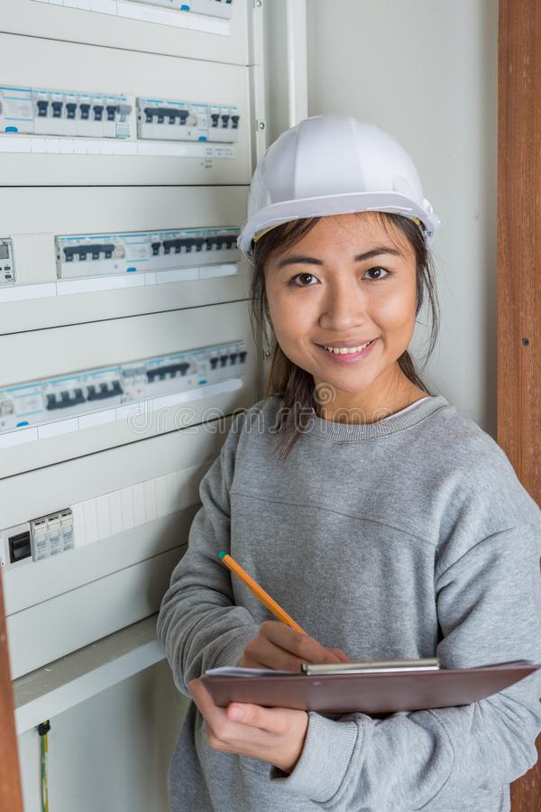Female electrician working on electical fuse board stock images