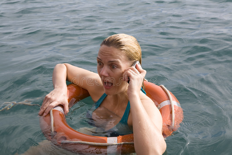 Female in emergency with lifebuoy and mobile phone stock photo