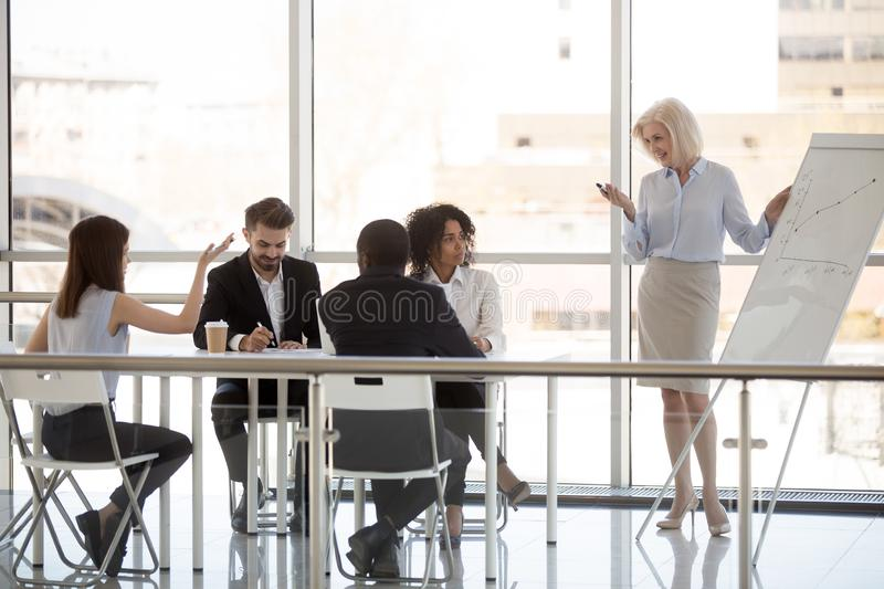 Female employee ask question to middle-aged coach at company meeting royalty free stock photos