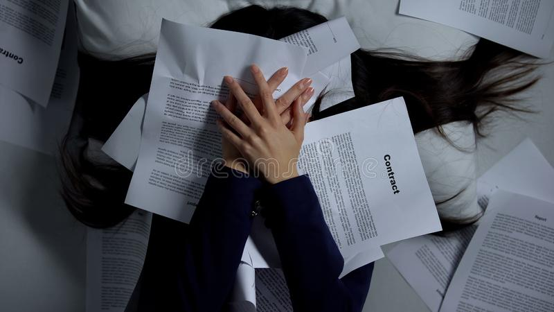Female employee covering herself with documents, despaired of workload, burnout. Stock photo stock images