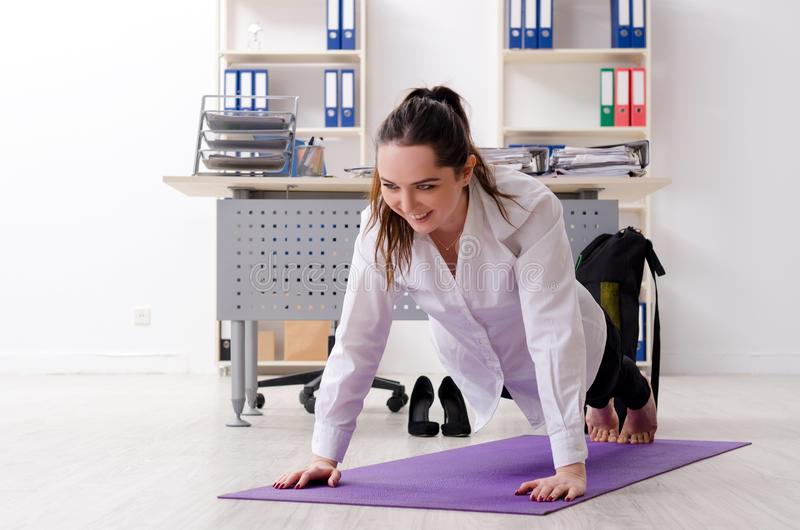 The female employee doing sport exercises in the office stock image