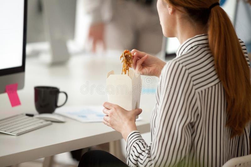 Female employee eating Asian noodles during office work break. Back close up view of female employee eating Asian food from takeaway box using chopsticks, worker stock images
