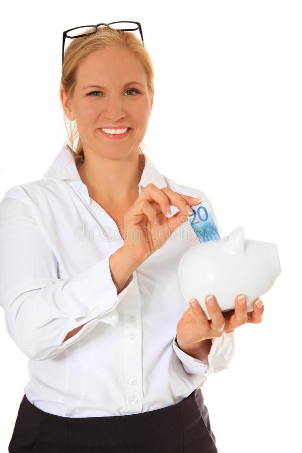Female employee putting money in piggy bank royalty free stock images