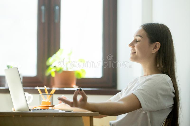 Female employee relaxing in office during a coffeebreak. Office yoga concept stock photography