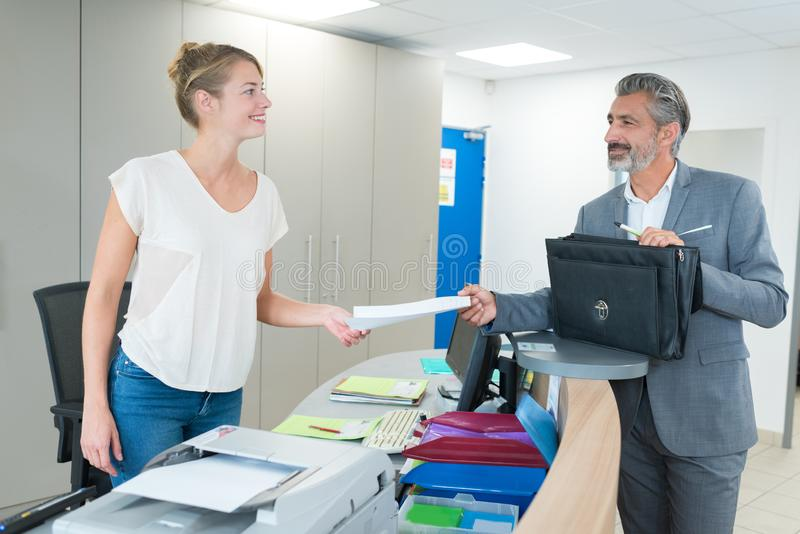 Female employee show pack documents to busy businesman. Female employee show pack of documents to busy businesman stock photo