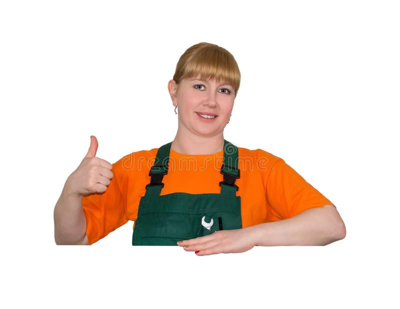 Female employee and space for inscriptions. Young woman in a work overalls holds thumb up, standing over empty space without inscriptions, isolated on white stock image