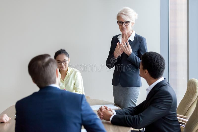 Female employee standing making speech at briefing stock photography