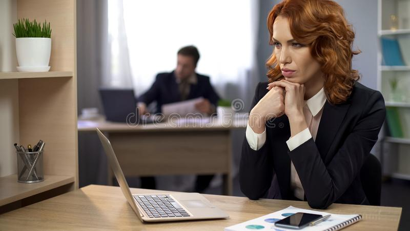 Female employee in suit sitting at work desk and thinking about project, office. Stock photo royalty free stock photos