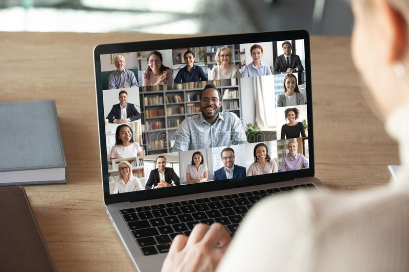 Female employee talk on video call with colleagues. Back view of female employee speak talk on video call with diverse multiracial colleagues on online briefing royalty free stock photos